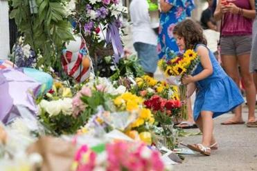 A young girl left flowers at the memorial outside the Emanuel African Methodist Episcopal Church on Friday.